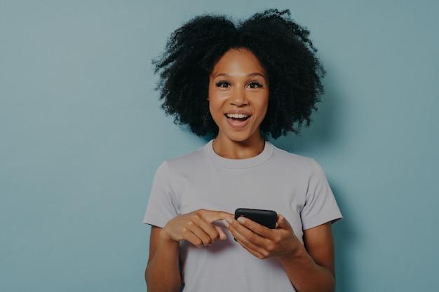 Mooi gelukkig meisje met een donkere huidskleur die moderne smartphone vasthoudt en online met een vriend chat