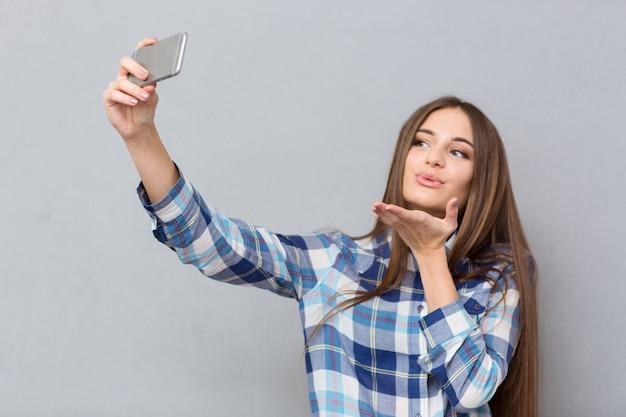 Mooi gelukkig meisje met lang haar in geruit overhemd dat selfie maakt met behulp van mobiele telefoon die een luchtkus stuurt