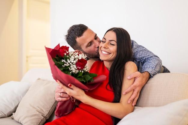 Mooi, gelukkig, positief paar omarmen, boeket van rode rozen vasthouden, 14 februari gelukkige valentijnsdag.