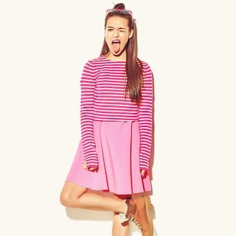 Mooi gelukkig schattige lachende brunette vrouw meisje in casual kleurrijke hipster zomer roze kleding met rode lippen geïsoleerd op wit met haar tong