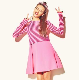 Mooi gelukkig schattige lachende brunette vrouw meisje in casual kleurrijke hipster zomer roze kleding met rode lippen geïsoleerd op wit vredesteken tonen