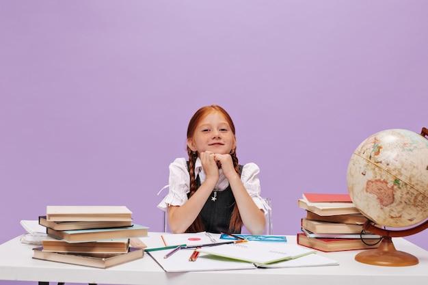 Mooi gember schattig schoolmeisje met staartjes in stijlvol schooluniform glimlachend en kijkend naar de voorkant op geïsoleerde muur