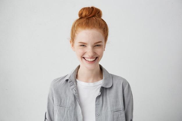 Mooi gember sproeterig meisje met mysterieuze glimlach poseren binnenshuis op lege grijze muur. mooie vrouw met haarbroodje breed glimlachend, witte rechte tanden tonen, genieten van vrije tijd thuis