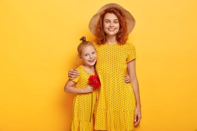Mooi gembermeisje met rode bloem omhelst moeder