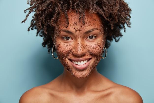 Mooi gemengd ras vrouw heeft huid scrub op gezicht, lacht zachtjes, maakt cosmetische maskers van koffie, heeft krullend kapsel, blote schouders, geïsoleerd over blauwe muur