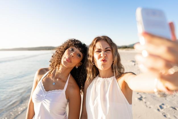 Mooi gemengd ras vrouwelijk paar dat gezichten maakt die zelfportret op strand doen