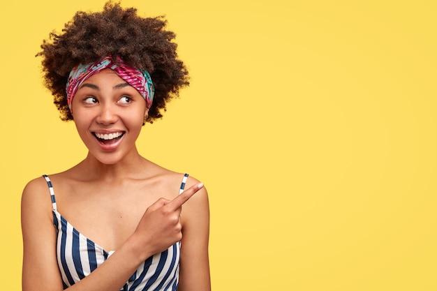 Mooi gemengd ras vrouwtje met knapperig haar, heeft een zachte glimlach, laat je iets aangenaams zien, wijst met wijsvinger op blanco gele muur. charmante afro-amerikaanse vrouw vormt binnen