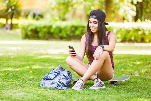 Mooi gemengd rasmeisje die slimme telefoon bekijken