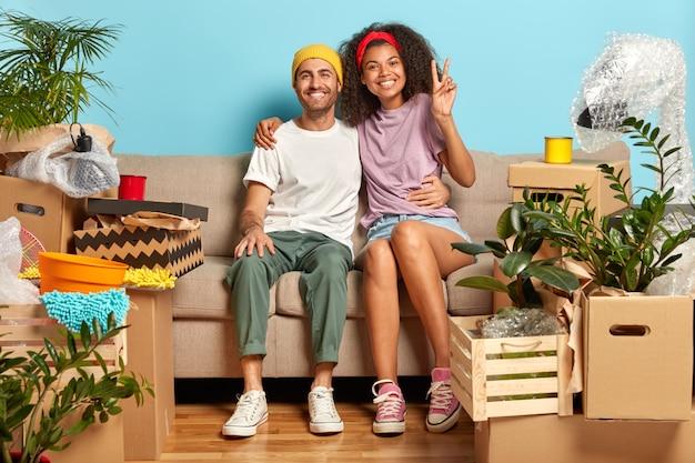 Mooi gemengd raspaar knuffelt op de bank, voelt zich tevreden, verheugt zich bij het verhuizen naar een nieuw huis