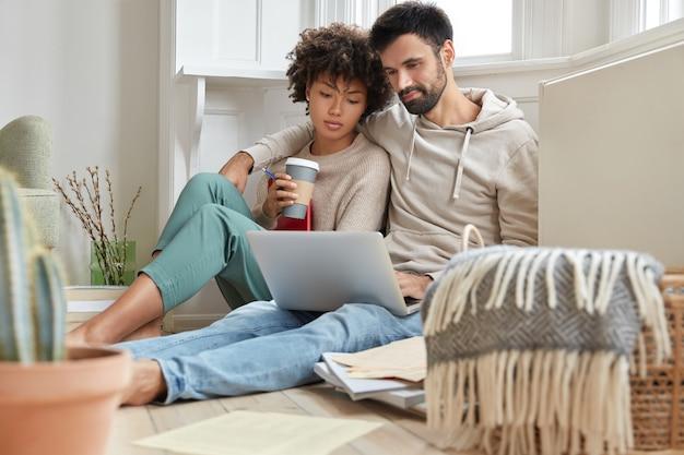 Mooi gemengd raspaar omhelst elkaar, zit op vloer, voelt zich ontspannen terwijl film op laptop computer kijkt