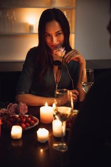 Mooi gepassioneerd paar met een romantisch diner bij kaarslicht thuis, vrouw ruiken een bloem