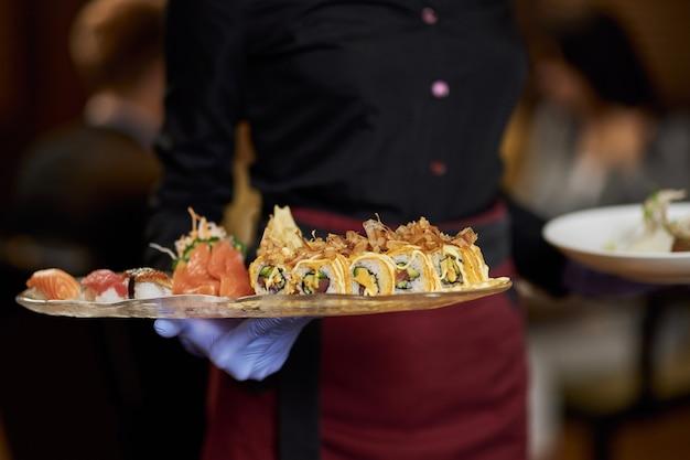 Mooi gerangschikte sushi op een bord dat wordt bezorgd door serveerster?