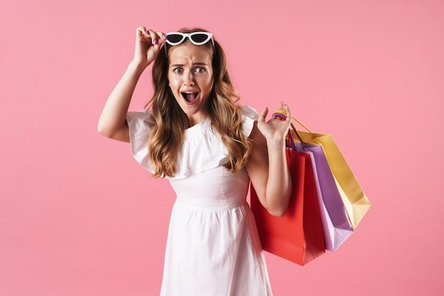 Mooi geschokt jong blond meisje met een zomerjurk die geïsoleerd over een roze muur staat en boodschappentassen draagt