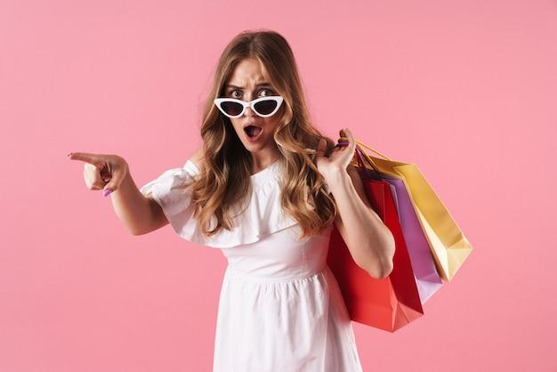 Mooi geschokt jong blond meisje met een zomerjurk die geïsoleerd staat over een roze muur, boodschappentassen draagt en wegwijst