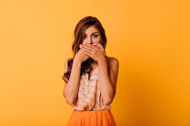 Mooi geschokt meisje in zomer outfit poseren op helder. modieuze vrouw met elegant kapsel dat mond behandelt met handen.