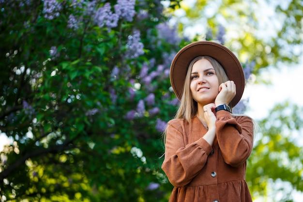 Mooi gevormd langharig meisje in de hoed op een achtergrond van lila bloemen