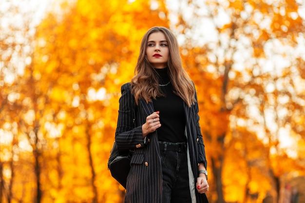 Mooi gevormd modieus meisje met rode lippen in een mode kleding met een blazer en een trui met een leren rugzak wandelingen in het park met oranje bladeren bij zonsondergang