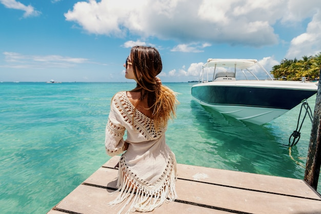 Mooi gevormde blanke brunette met lang haar in zomerjurk zittend op pier