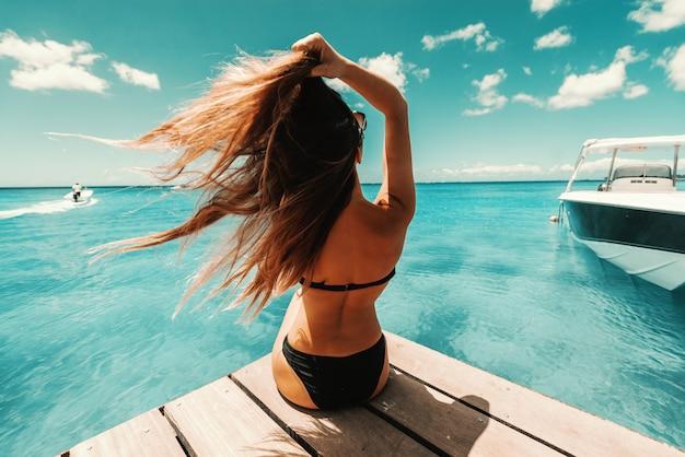 Mooi gevormde brunette in zwembroek en met zonnebril zittend op de pier en genieten van zonnig weer en de oceaan. teruggedraaid.
