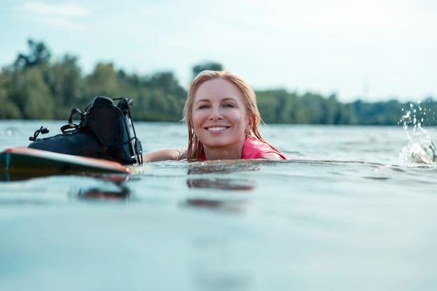 Mooi gezicht. close-upportret van een mooie glimlachende kaukasische vrouw met los blond haar die in het water naast haar wakeboard drijven