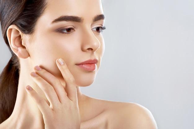 Mooi gezicht. mooie vrouw met natuurlijke make-up raakt eigen gezicht. meisje met schone frisse huid. detailopname. cosmetologie.