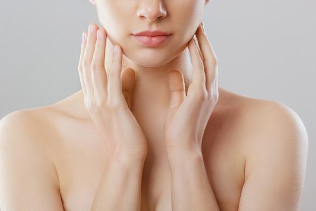 Mooi gezicht. mooie vrouw met natuurlijke make-up raakt eigen gezicht