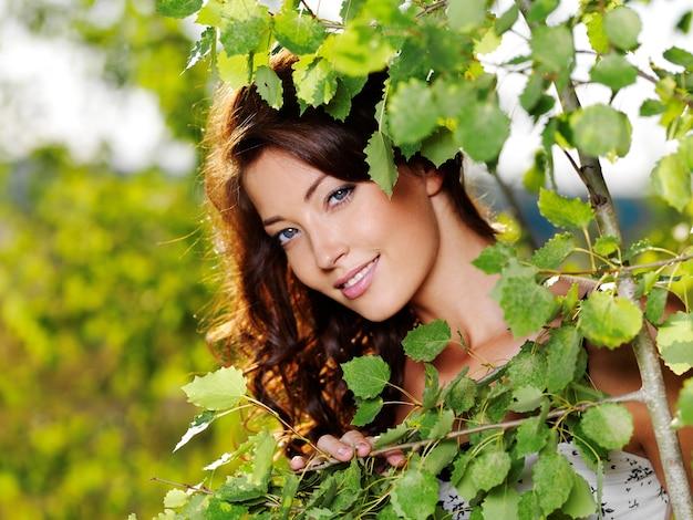 Mooi gezicht van de jonge vrouw die zich voordeed in de buurt van de groene boom op aard