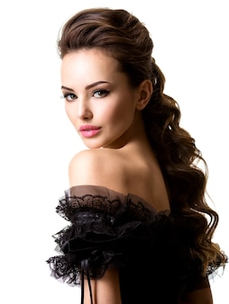 Mooi gezicht van een jonge sexy vrouw in zwarte jurk poseren op witte muur