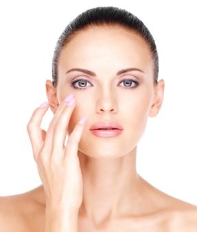 Mooi gezicht van een mooie vrouw die de huid in de buurt van de ogen aanraakt - geïsoleerd op wit