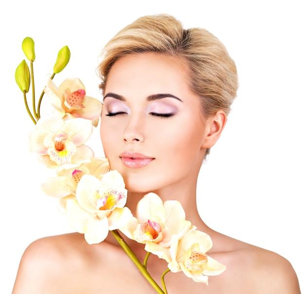 Mooi gezicht van jonge mooie vrouw met een gezonde huid en roze bloemen op lichaam - geïsoleerd op wit