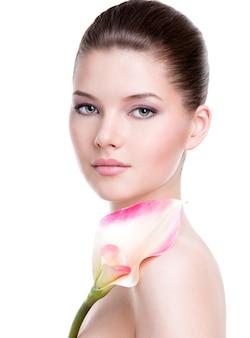 Mooi gezicht van jonge mooie vrouw met een gezonde huid en roze bloemen op lichaam - geïsoleerd op wit.