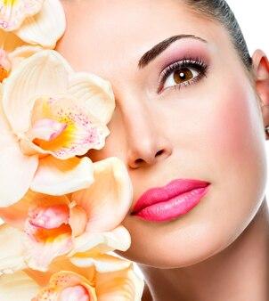 Mooi gezicht van jonge mooie vrouw met een gezonde huid en witte bloemen geïsoleerd op wit