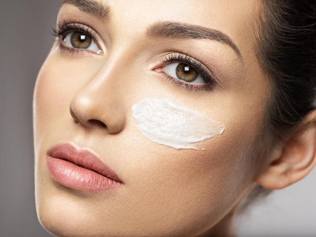 Mooi gezicht van jonge vrouw met cosmetische crème-uitstrijkje op gezicht in de buurt van oog. huid zorg concept. schoonheidsbehandeling concept.