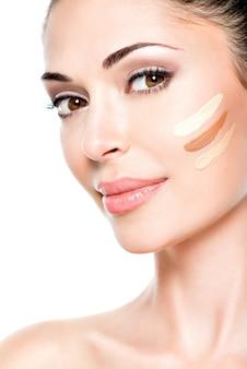 Mooi gezicht van jonge vrouw met cosmetische foundation op een huid.