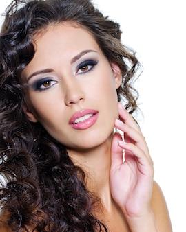 Mooi gezicht van jonge vrouw met schone huid. meisje met lange krullende haren. heldere oogmake-up