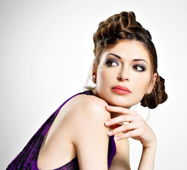 Mooi gezicht van jonge vrouw met stijlvol kapsel met pigtails-ontwerp, vormt in de studio