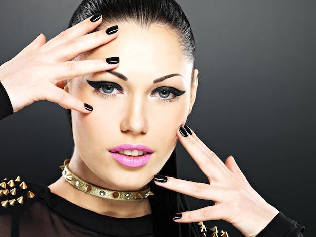 Mooi gezicht van mode vrouw met zwarte nagels en lichte make-up. sexy stijlvol meisje met armband doornen in de nek