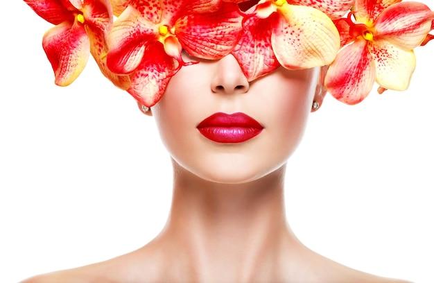 Mooi gezicht van vrouw met felle lippenstift op lippen en roze bloemen geïsoleerd op wit