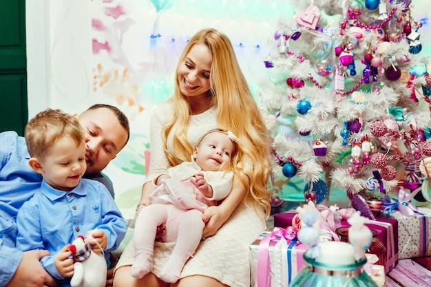 Mooi gezin met kinderen in warme truien vormt voor een muur en een rijke kerstboom