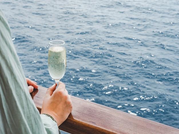 Mooi glas met een drankje op zeegolven en zonnestralen. bovenaanzicht, close-up. concept van vrije tijd en reizen