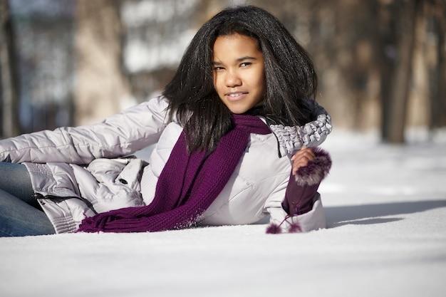 Mooi glimlachend amerikaans zwart wijfje dat in sneeuw in openlucht ligt