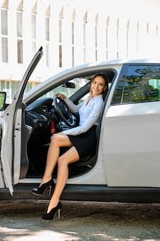Mooi glimlachend donkerbruin meisje achter het stuur van een auto
