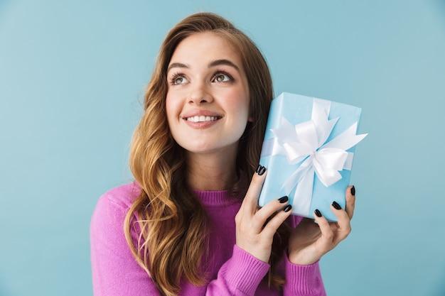 Mooi glimlachend jong meisje met vrijetijdskleding die geïsoleerd over een blauwe muur staat en de huidige doos toont