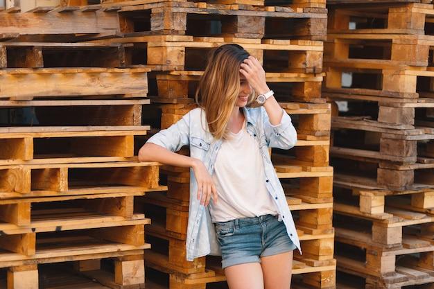 Mooi glimlachend meisje, dat jeans, borrels en overhemd het stellen op houten achtergrond draagt