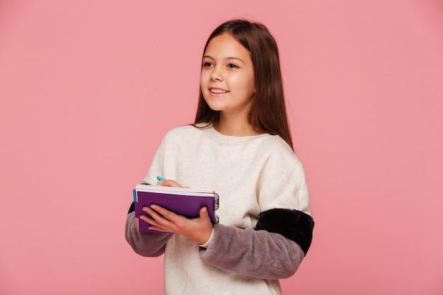 Mooi glimlachend meisje dat opzij en in geïsoleerd notitieboekje schrijft schrijft