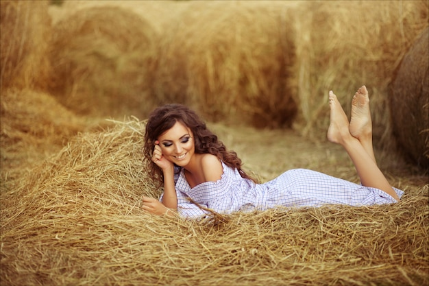 Mooi glimlachend meisje dichtbij een hooibaal op het platteland. meisje dat op de hooiberg ligt
