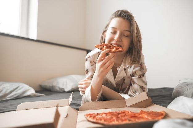 Mooi glimlachend meisje in een pyjama ligt in het bed van een huis met een doos pizza