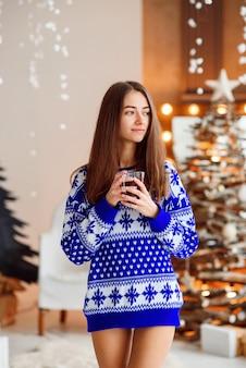 Mooi glimlachend meisje in een warme vakantiesweater met een kop warme thee