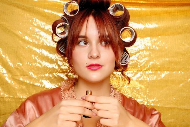 Mooi glimlachend meisje in haarkrulspelden die op goud worden geïsoleerd. portret van jonge mooie sexy lachende vrouw. vrouw met lippenstift