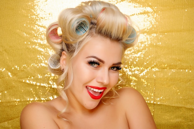 Mooi glimlachend meisje in haarkrulspelden die op goud worden geïsoleerd. portret van jonge mooie sexy lachende woman